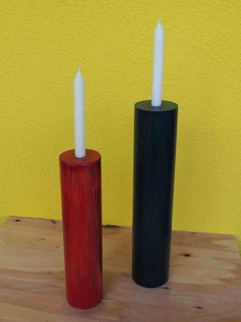 zwei Kerzenleuchter in den Farben rot und blau auf einer Holztafel mit gelbem Hintergrund