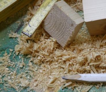 Hobelspäne, Bleistift und Zollstock auf der Werkbank im Atelier